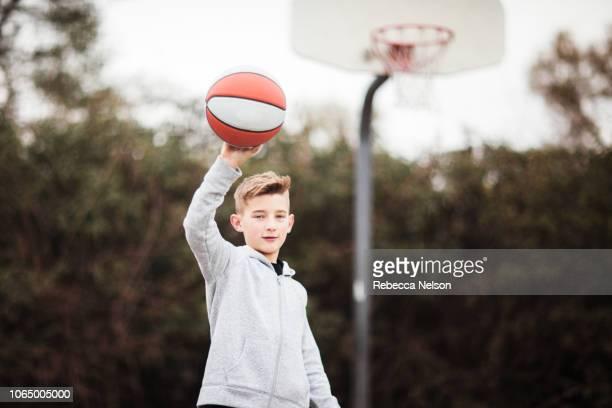 Pre-teen boy palming basketball on playground basketball court