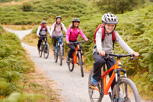 Pre-teen boy riding mountain bike with his sister and parents during a family camping trip, close up 1077690554