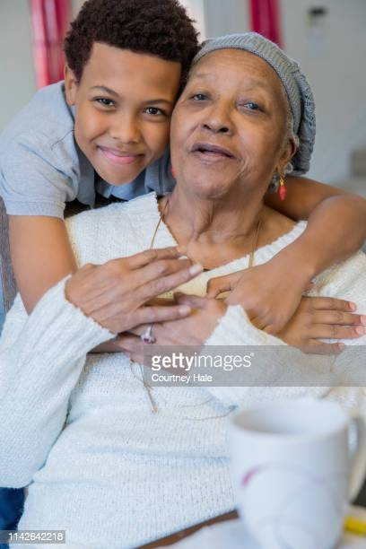 preteen boy smiles while hugging elderly great grandmother during nursing home visit - great grandmother stock pictures, royalty-free photos & images