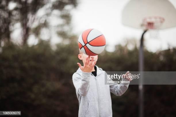 pre-teen boy spinning basketball on fingertip