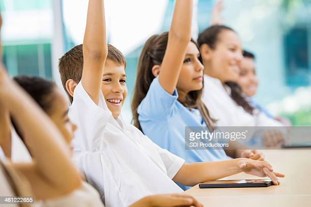 Preteen elementary school students raising hands to answer question