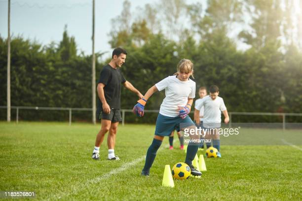 pre-teen female goalkeeper practicing dribbling drills - sports training drill stock pictures, royalty-free photos & images