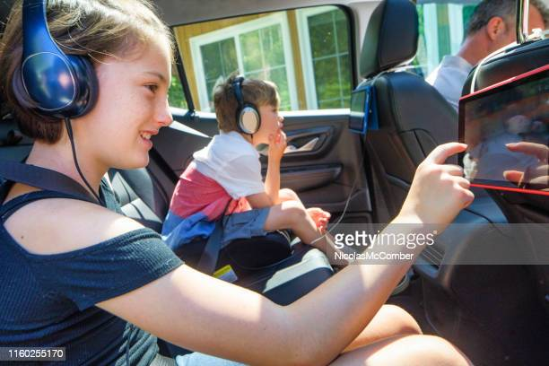 preteen girl and younger brother using tablet inside car during a road trip - digital native stock pictures, royalty-free photos & images