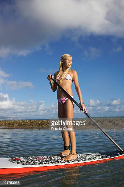 a pre-teen girl at paia beach, maui, hawaii stand-up paddling her surf board. - category:census-designated_places_in_honolulu_county,_hawaii stock pictures, royalty-free photos & images