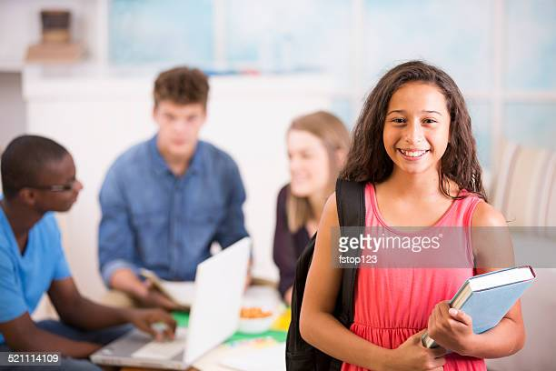 Preteen girl backpack, textbook. Teens study together at home.