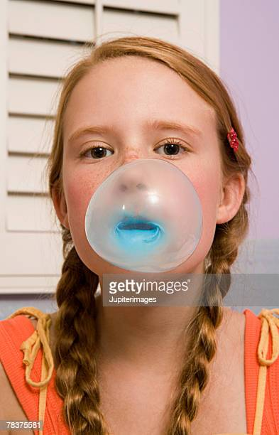 Preteen girl blowing bubble