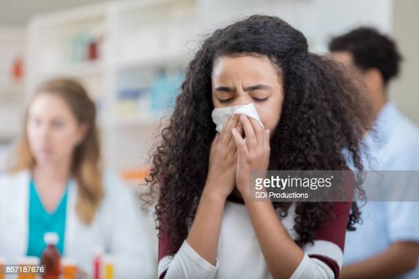 preteen girl coughing into a tissue at pharmacy - covering stock pictures, royalty-free photos & images