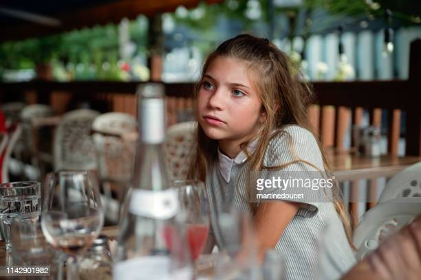 Preteen girl day dreaming at restaurant terrace.