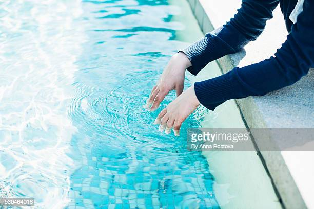 Preteen girl dipping hands in fountain water