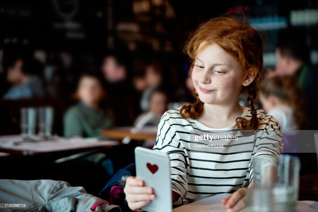 Preteen girl doing selfies at a restaurant table. : Stock Photo