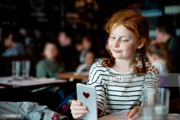 "preteen girl doing selfies at a restaurant table. - ""martine doucet"" or martinedoucet stock pictures, royalty-free photos & images"