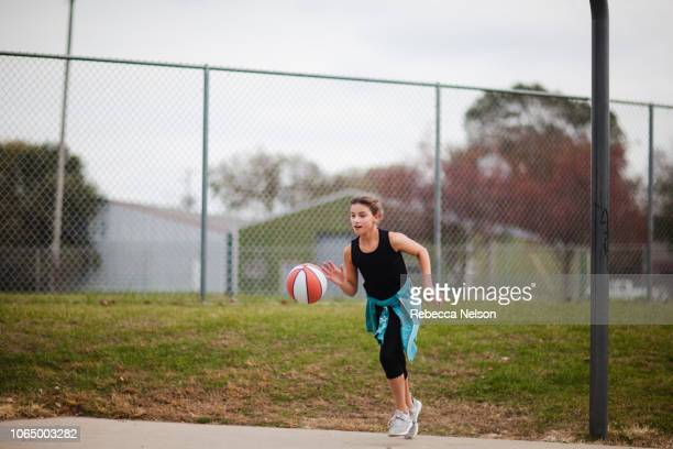 pre-teen girl dribbling basketball down basketball court - dribbling sports stock pictures, royalty-free photos & images