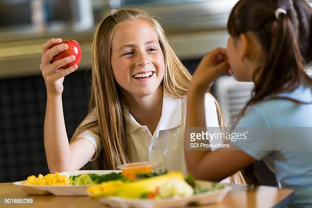 preteen girl eating healthy lunch with friend in school cafeteria - kid girl eating apple stock photos and pictures
