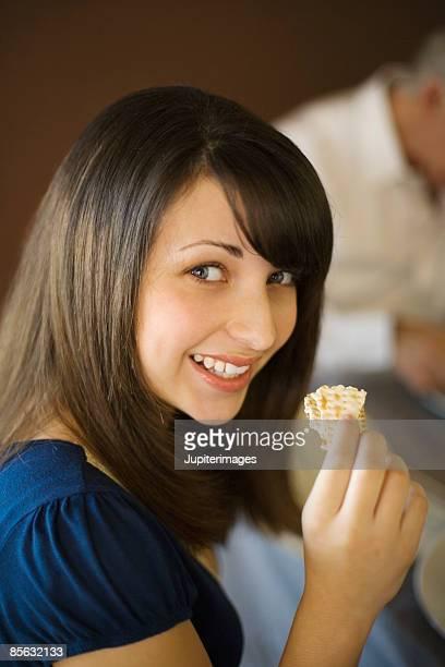 Preteen girl eating matzoh