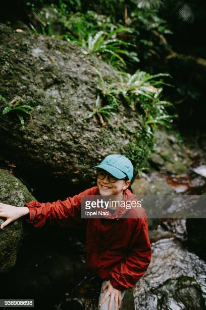 Pre-teen girl enjoying hiking in jungle river, Okinawa, Japan
