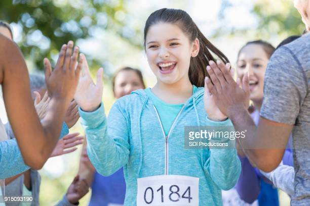 Preteen girl gives high fives after charity race