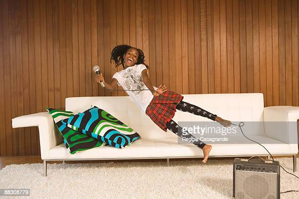 Pre-teen girl holding microphone jumping onto couch