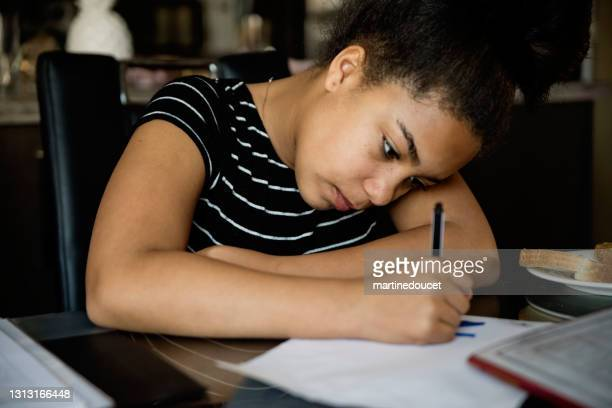"""preteen girl homeschooling on the dining room table. - """"martine doucet"""" or martinedoucet stock pictures, royalty-free photos & images"""