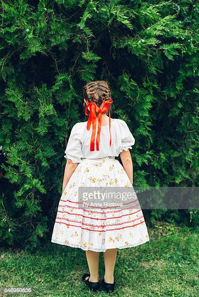 Preteen girl in Hungarian traditional folk costume back to camera in front of green tree