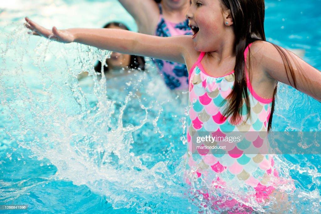 Preteen girl in pool splashing others. : Stock Photo