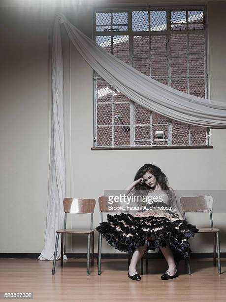 Pre-teen girl (10-12) in ruffled party dress looking bored sitting in school hall