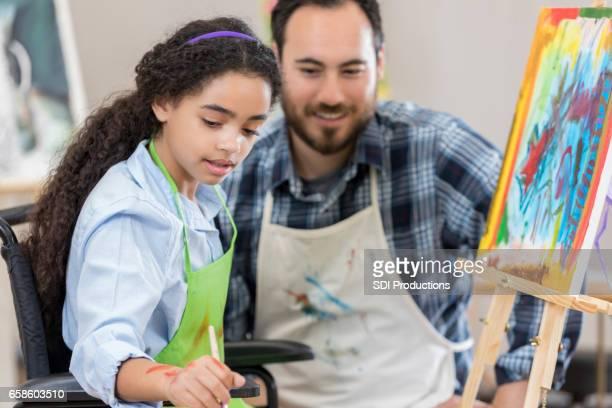 Preteen girl in wheelchair takes art lesson