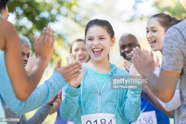 preteen girl is all smiles as she finishes a charity race - charity benefit stock pictures, royalty-free photos & images