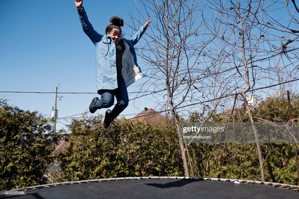 Preteen girl jumping on trampoline outdoors in springtime. : Stock Photo