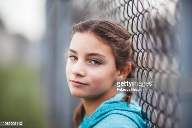 pre-teen girl leaning agains chainlink fence on playground