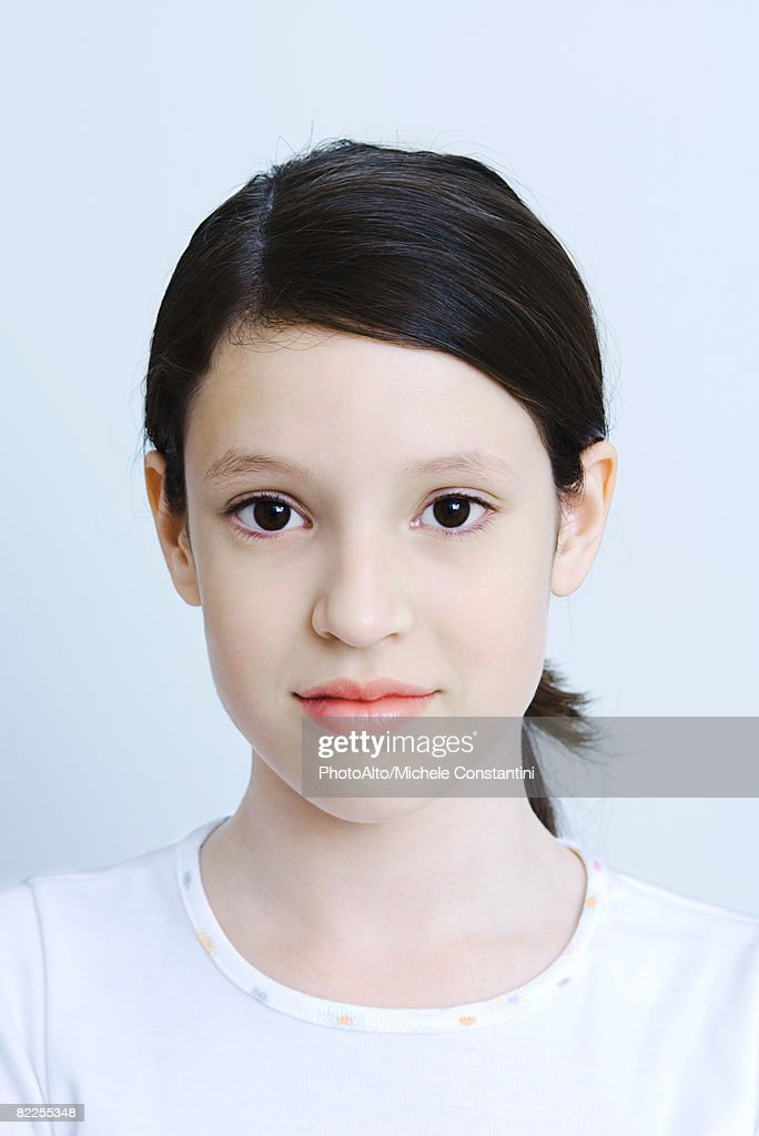 Preteen girl looking at camera, head and shoulders, portrait : Stock Photo