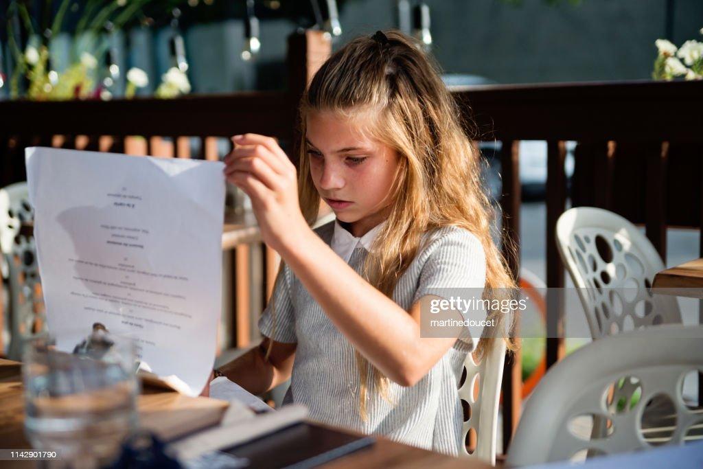 Preteen girl looking at the menu at restaurant terrace. : Stock Photo