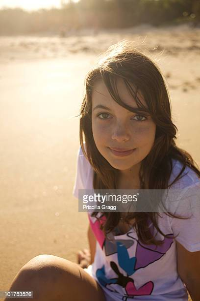 A pre-teen girl looks up at the camera and smiles at Paia Beach, Maui, Hawaii as the sun rises.