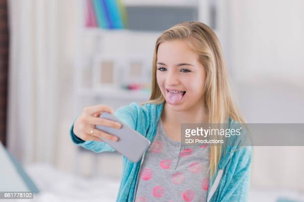 preteen girl makes a silly face while taking selfie - little girl sticking out tongue stock photos and pictures