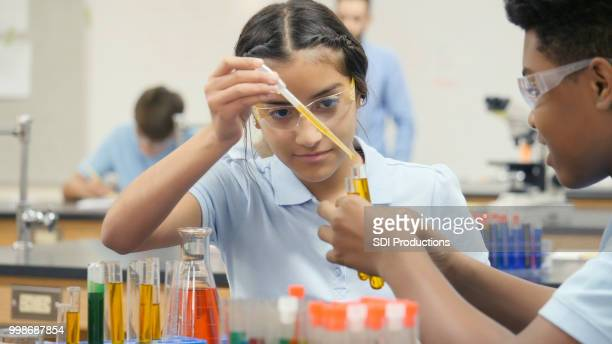 preteen mädchen führt chemie experiment mit übungspartner - schüler der junior high school stock-fotos und bilder