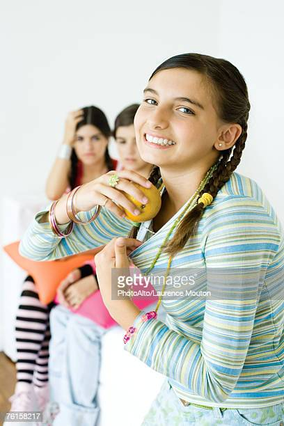 preteen girl putting apples in shirt while older friends watch in background - young girl breasts stock pictures, royalty-free photos & images