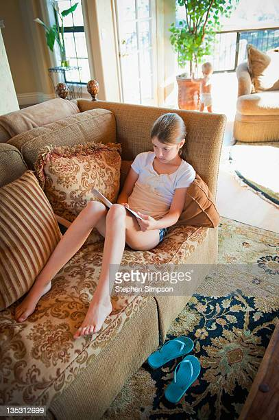 pre-teen girl reading on the couch - budding tween stock photos and pictures