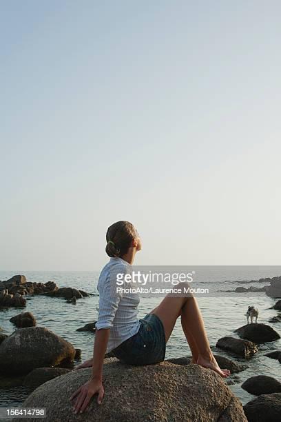 Preteen girl relaxing on rock, enjoying view of ocean