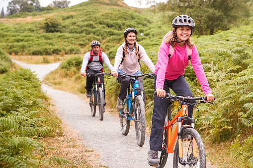 Pre-teen girl riding mountain bike with her parents during a family camping trip, close up 1077691056