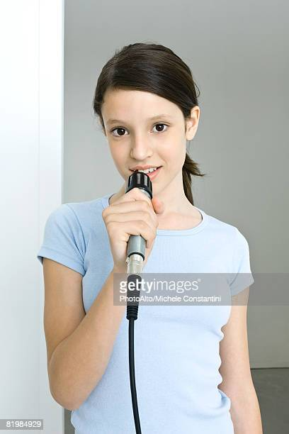 preteen girl singing into microphone, smiling at camera - only girls stock pictures, royalty-free photos & images
