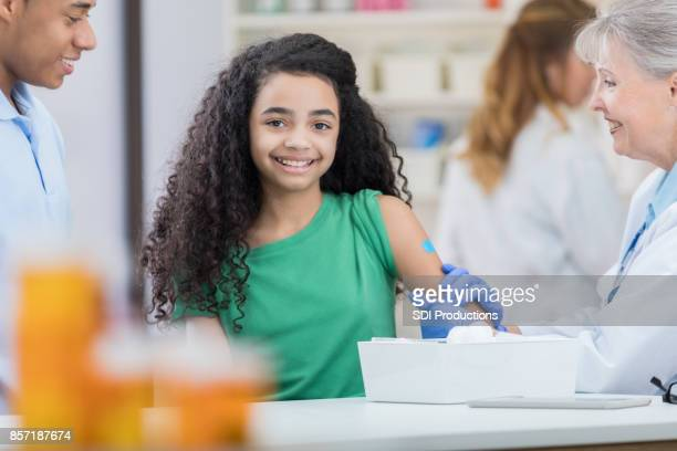 preteen girl smiles for camera after flu vaccination at pharmacy - flu shot stock photos and pictures