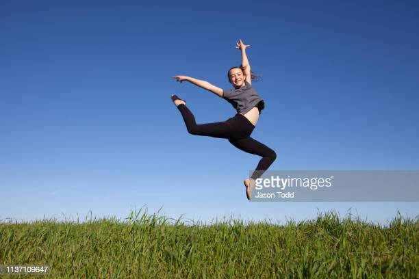 preteen girl smiling, doing double attitude leap above grass - jason todd stock photos and pictures