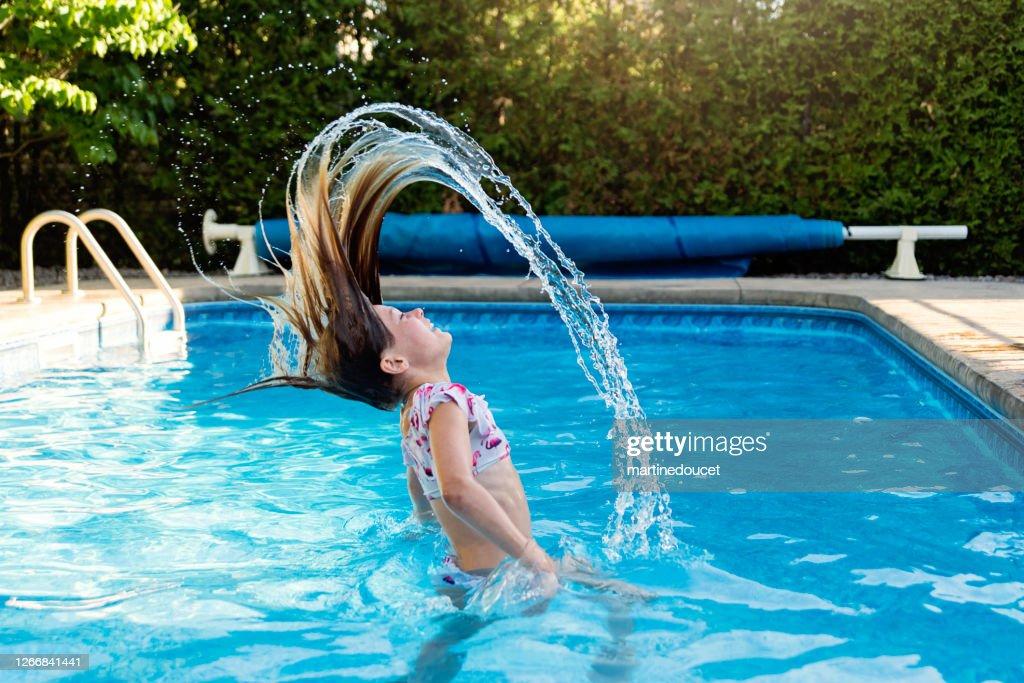 Preteen girl splashing hair in backyard pool. : Stock Photo