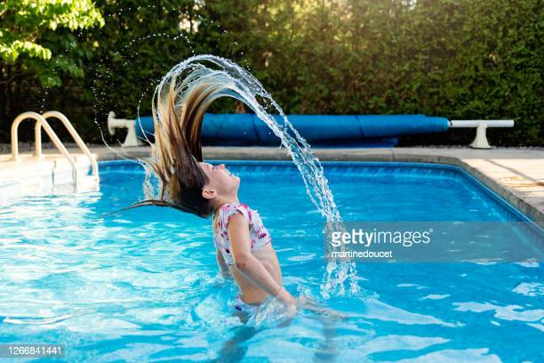 """preteen girl splashing hair in backyard pool. - """"martine doucet"""" or martinedoucet stock pictures, royalty-free photos & images"""