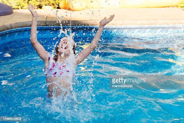 """preteen girl splashing water in backyard pool. - """"martine doucet"""" or martinedoucet stock pictures, royalty-free photos & images"""