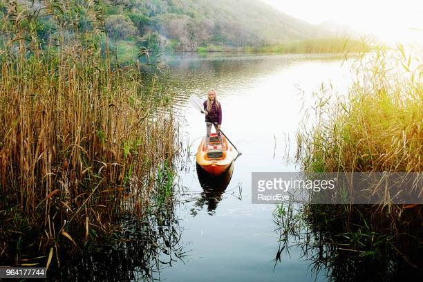 Preteen girl stands up as she paddles a canoe