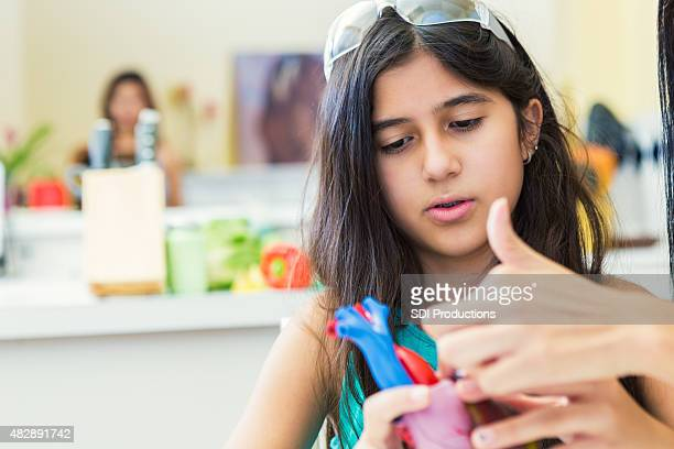 Preteen girl studying science heart model during homeschool class