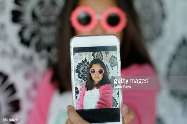 Preteen girl taking a self portrait with smart phone