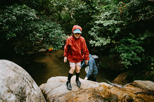 Pre-teen girl trekking in jungle river in rain, Ishigaki Island, Okinawa, Japan - gettyimageskorea