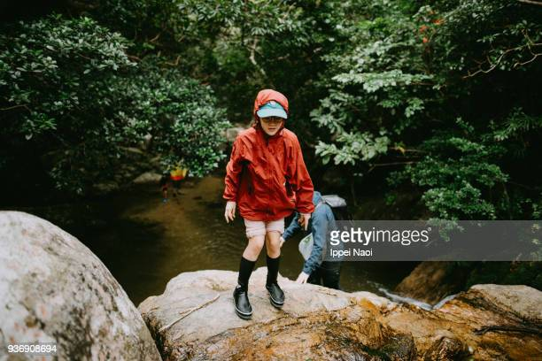 Pre-teen girl trekking in jungle river in rain, Ishigaki Island, Okinawa, Japan