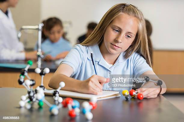 preteen girl using atom educational toy in science class - physics stock pictures, royalty-free photos & images